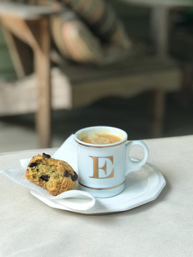 WOODBRIDGE, NEW JERSEY / UNITED STATES - July 11, 2018: A Williams Sonoma mug filled with espresso sits on a saucer with a chocolate chip muffin