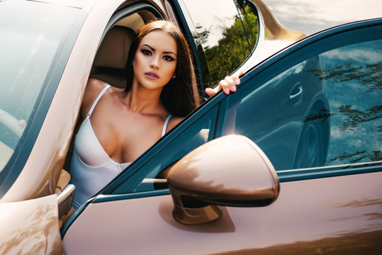 Young brunette lady in glamorous lingerie with sexy bust sitting at driver position in golden expensive luxury car. Sensual brunette woman with long hair in sexy underwear seating in car.