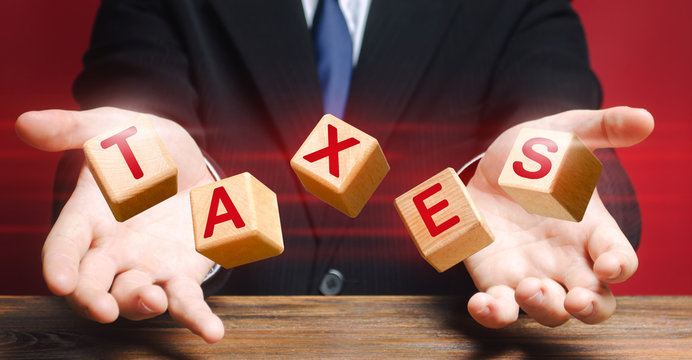 Cubes thrown by official or businessman make up word Taxes. Income declaration, tax payment, State and Local taxation. Management financial reporting in business, deductions exemptions, tax holidays.