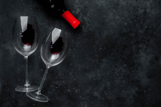 Bottle of red wine and glasses with  wine on a stone background. Top view with copy space.