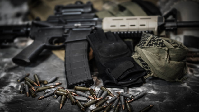 Close up of equipment carried by a Military Contractor featuring an AR15, ammunition, gloves, and body armor.