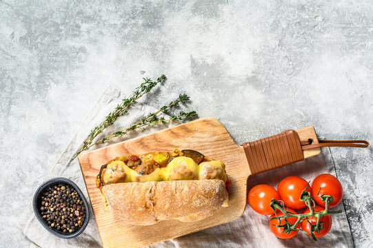 ciabatta sandwich with meatballs, cheese and tomato sauce. Gray background. Top view. Copy space