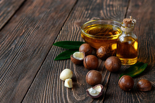 Organic macadamia oil and macadamia nuts on a wooden background.