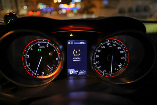 Warning lights flash on the car dashboard. Low tire pressure error sign.