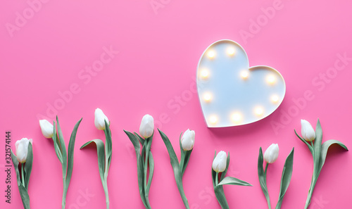 St Valentine's day pink background. Wave parallel geometric line of white tulip flowers. Lightboard in heart shape with illuminated lights. Flat lay, top view, trendy Valentine design background.