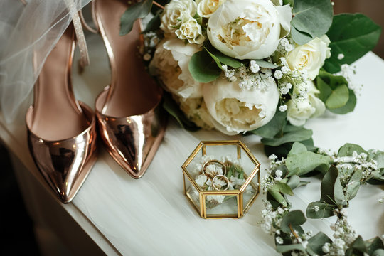 Wedding accessories on the dressing table: a bridal bouquet of white peonies, wedding rings in a glass box, gold shoes. wedding morning preparation