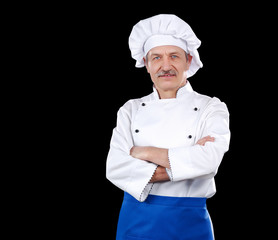Smiling cook with crossed hands against black background