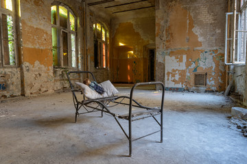 Foto op Textielframe Oud Ziekenhuis Beelitz old dirty abandoned room with a steel bed frame and an old doll on a pillow