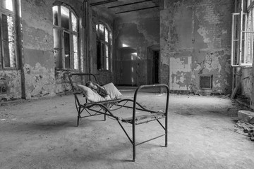 black and white, old dirty abandoned room with a steel bed frame and an old doll on a pillow