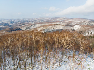 Mountains of Hokkaido in early winter with blue skies and sun shinning down
