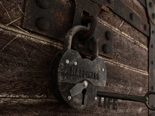 Key to happiness - Key with a secret formed by the word life opening an old padlock with the inscription happiness that is closing a wooden chest. 3D illustration