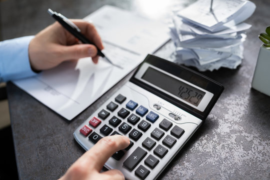 Businessman Calculating Expenses In Office