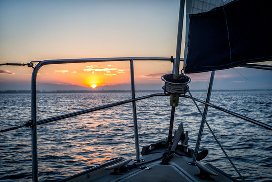 Sailing toward sunrise or sunset on sailboat on the ocean heading for shore in Texas