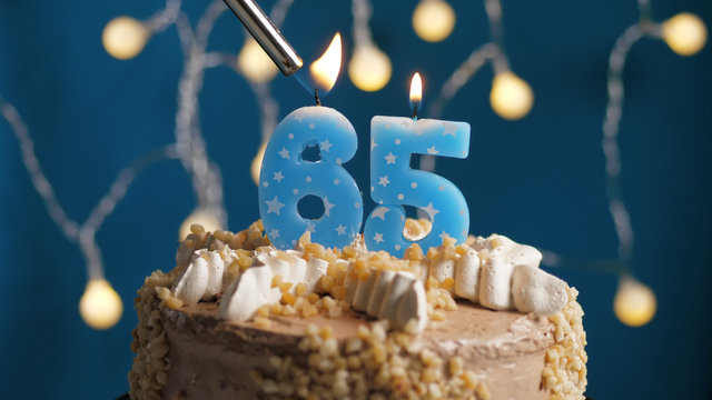 Birthday cake with 65 number candle on blue backgraund set on fire by lighter. Close-up