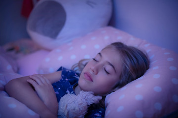 Little girl fast asleep in her bed