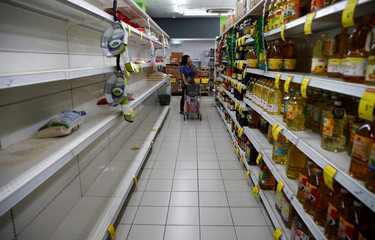 A packet of rice is pictured on an empty shelf as people stock up on food supplies, after Singapore raised coronavirus outbreak alert level to orange, at a supermarket in Singapore