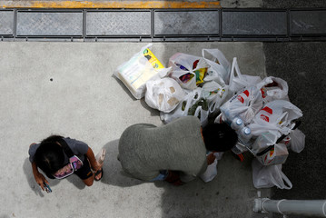 A woman packs her grocery shopping as she stocks up on food supplies, after Singapore raised coronavirus outbreak alert level to orange, outside a supermarket in Singapore