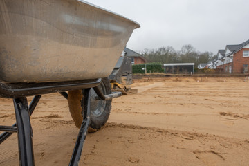 a building site a wheelbarrow stands on levelled gravel