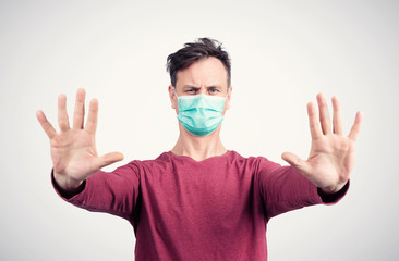 Man in a red T-shirt and a mask respirator extended his hands in front of him with open hands in a gesture of stop. Attention virus concept