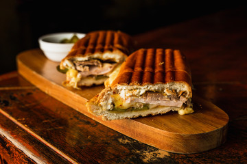 Papiers peints Snack Traditional cuban sandwich with cheese, ham and fried pork, served on a wooden board