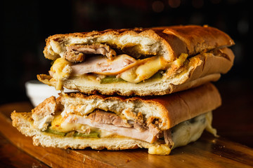 Foto auf Acrylglas Fastfood Traditional cuban sandwich with cheese, ham and fried pork, served on a wooden board