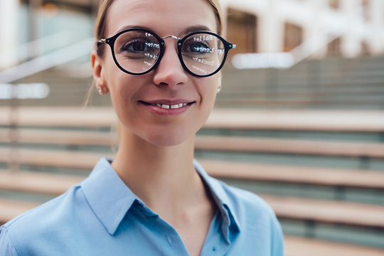Portrait of Caucasian female of 20 years old looking at the camera. Smiling young woman wearing stylish optical eyewear with smart reflection . Women's eye glasses with diopters, vision correction