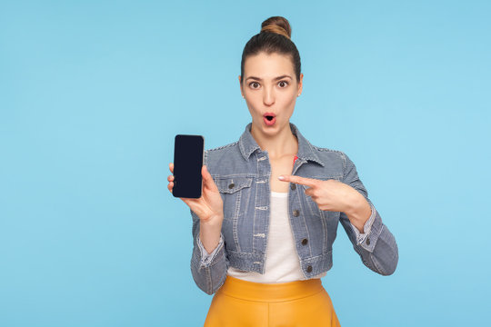 Portrait of funny amazed fashionably dressed woman with hair bun pointing at mobile phone and looking at camera with wide open mouth, shocked face. indoor studio shot isolated on blue background