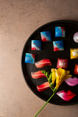 Overhead view of Collection of  Chocolate candy on dark plate and flowers