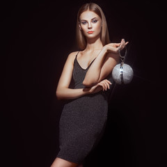 Beautiful young woman in Little black dress. Girl posing on a black background. Blonde girl with long healthy and shiny hair. Care and Beauty. Fashion photo. Glamour lady with a handbag of shiny gems