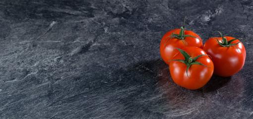 Frische, leuchtend rote Tomaten auf grauem Hintergrund (Arbeitsplatte), Banner rechts Wall mural