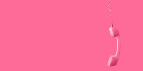Pink telephone receiver on pink background