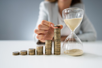Businesswoman With Hourglass And Stack Of Coins