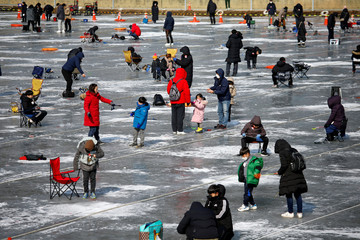 People wearing masks to prevent contacting a new coronavirus fish for trout on a frozen river during the Ice Festival in Hwacheon