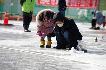 Mother and her child wearing masks to prevent contacting a new coronavirus, fish for trout  on a frozen river during the Ice Festival in Hwacheon