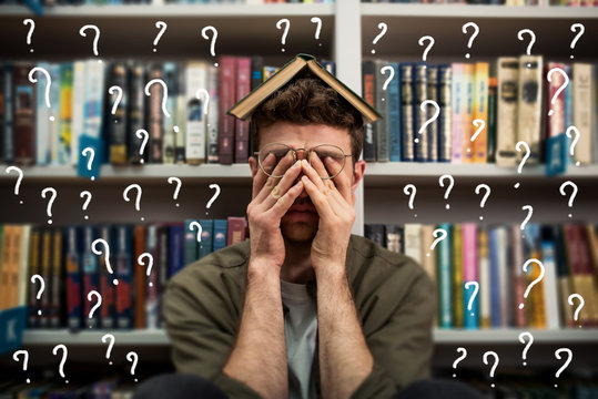 Tired university student has difficulty to study. Full of question mark. Concept of stress and difficulty