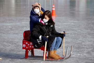 Mother and her child wearing masks to prevent contacting a new coronavirus fish for trout on a frozen river during the Ice Festival in Hwacheon