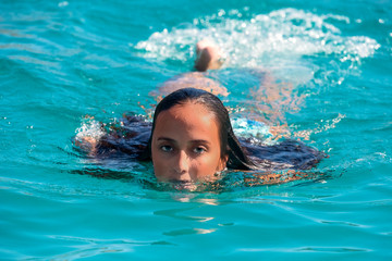 black hair mexican latina girl swimming in crystal sea waters