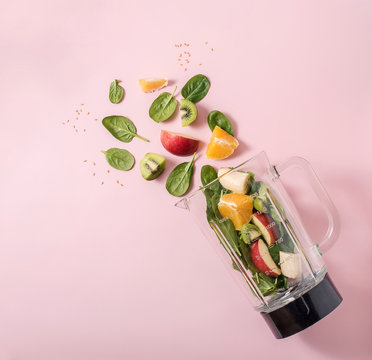 Smoothie ingredients in mixer, smoothie preparation with spinach, apple, orange, kiwi, healthy eating, detox and nutritional consultation concept