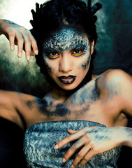 fashion portrait of pretty young woman with creative make up like a snake, halloween concept