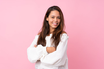 Young Brazilian girl over isolated pink background with arms crossed and happy