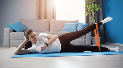 Young woman strengthening hips lying on side and lifting one leg using resistance band tracking time Fotomurales