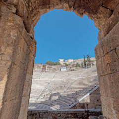 Athens Greece, Herodium ancient roman theater stands and anciennt temple through the main entrance arch