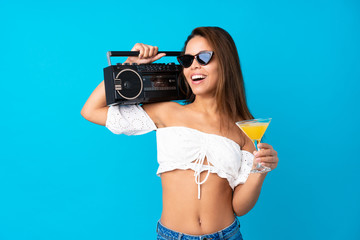 Young woman in summer holidays holding a radio over isolated blue background