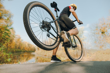 Action photo of a cyclist doing the trick in the park, lifting the rear wheel up. A man is extreme riding on the road in the park. Closeup photo of an extreme cyclist