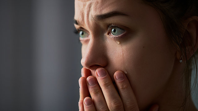 Sad desperate grieving crying woman with folded hands and tears eyes during trouble, life difficulties, depression and emotional problems