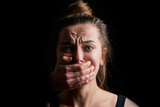 Stressed unhappy scared crying woman victim in fear with closed mouth on a dark black background suffering from domestic violence abuse