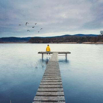 Frau sitzt einsam am See