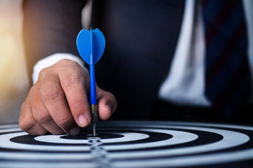 target and strategy concept, businessman focus to aim by throwing dart on targeting