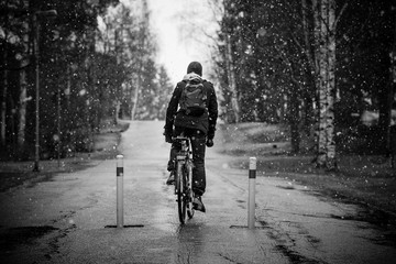 Black and white photo of a man riding a bicycle during snowfall