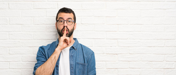 Handsome man with beard over white brick wall showing a sign of silence gesture putting finger in mouth